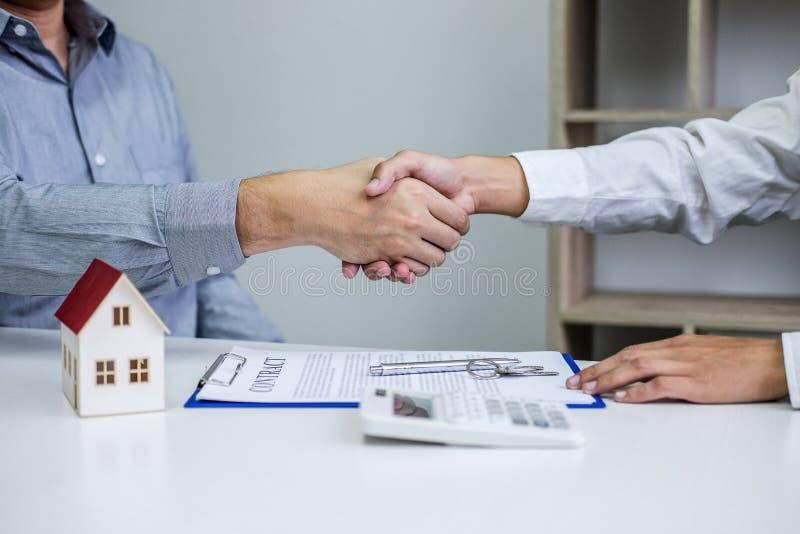 Агент и клиенты недвижимости тряся руки совместно празднуя законченный контракт после подписания о страховании жилья и стоковая фотография rf