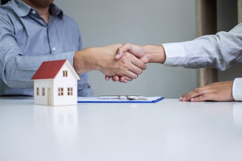 Агент и клиенты недвижимости тряся руки совместно празднуя законченный контракт после подписания о страховании жилья и стоковая фотография
