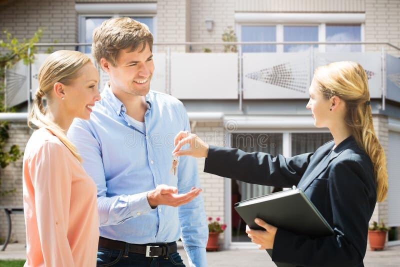 Агент недвижимости давая ключ дома к парам стоковое изображение