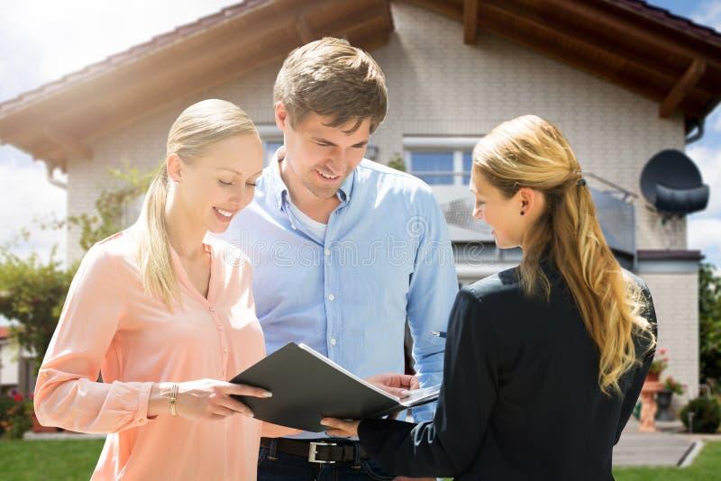 Агент недвижимости обсуждая документ с парами стоковое изображение rf