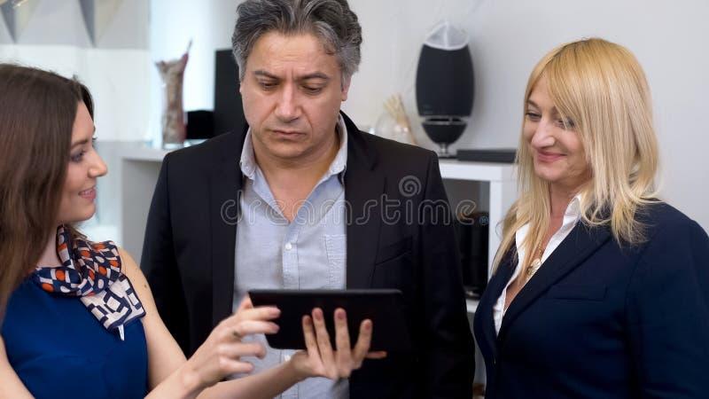 Агент недвижимости показывает фото квартиры на таблетке к покупателям, приобретении дома стоковые фото