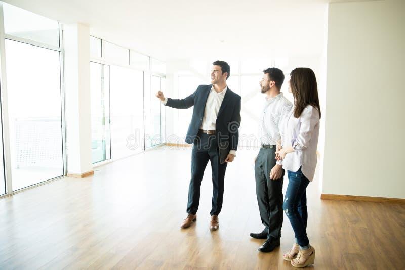 Агент недвижимости показывая новую квартиру к человеку и женщине стоковые изображения