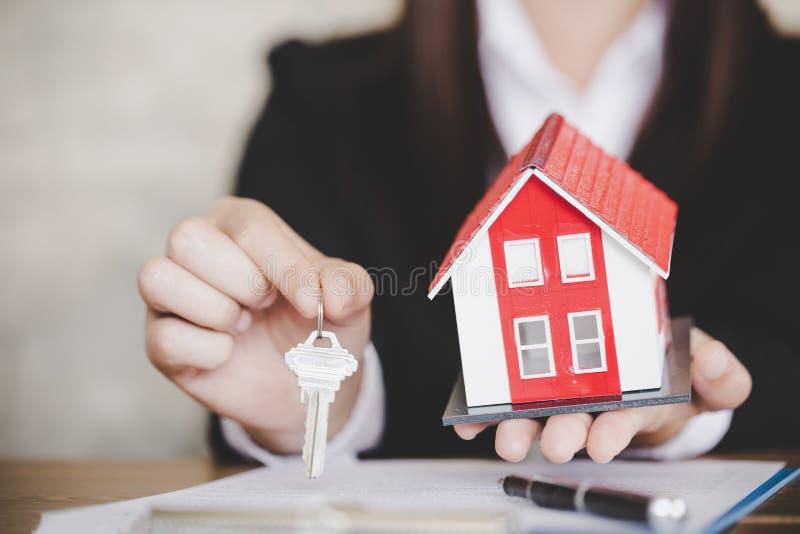 Агент недвижимости с моделью и ключами дома стоковые изображения