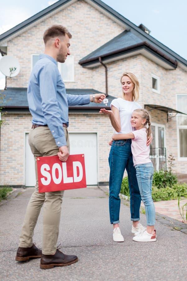 агент недвижимости с проданным знаком давая ключ молодой женщине стоковые изображения