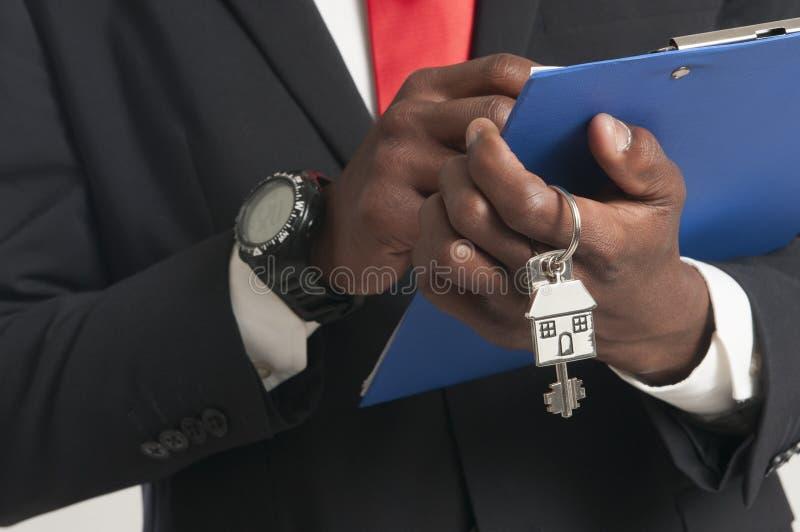 Агент недвижимости вручая над ключами дома стоковые изображения rf