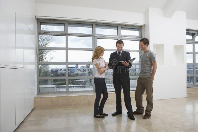 Агент недвижимости показывая парам новую квартиру стоковые фотографии rf