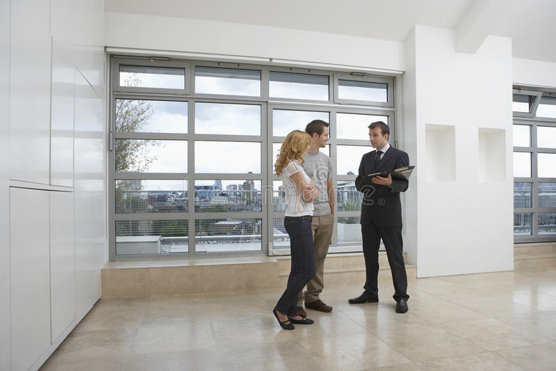 Агент недвижимости показывая парам новую квартиру стоковое фото rf