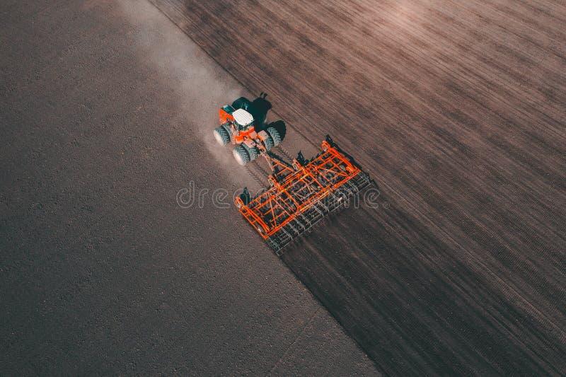 Аграрный промышленный трактор вспахивает поле почвы для засевать, воздушный взгляд сверху Культивирование земли, концепция сельск стоковое фото