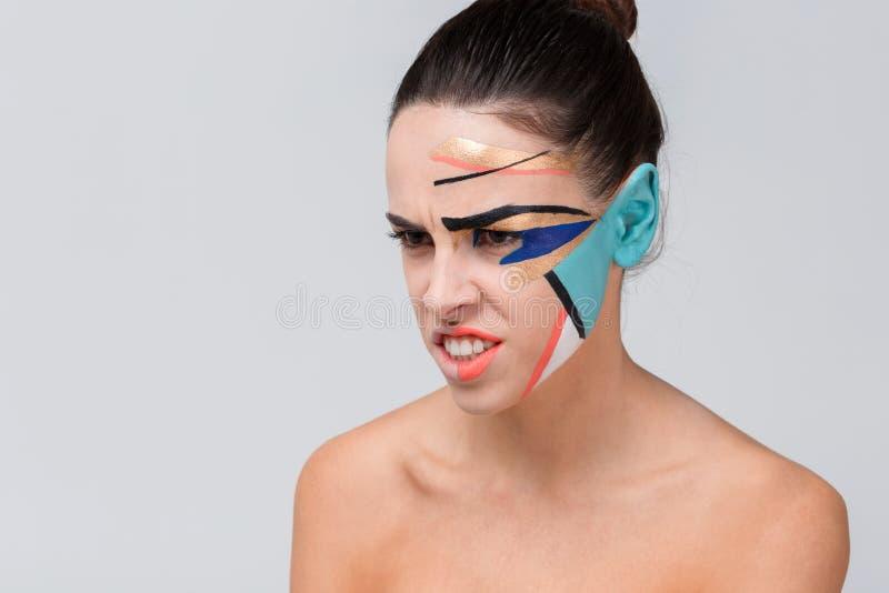 Агрессивная девушка, с чуть-чуть плечами и с красочным творческим геометрическим гримом на ее стороне стоковые изображения rf