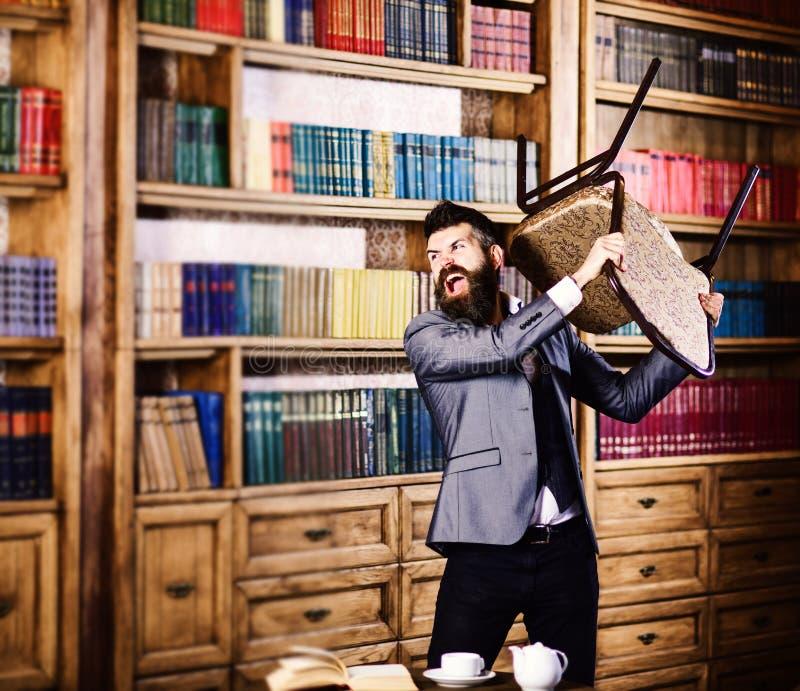 Агрессия, ненависть, слабонервная, отрицательная концепция эмоций Человек с сердитой стороной держит стул и губит библиотеку Боро стоковое изображение