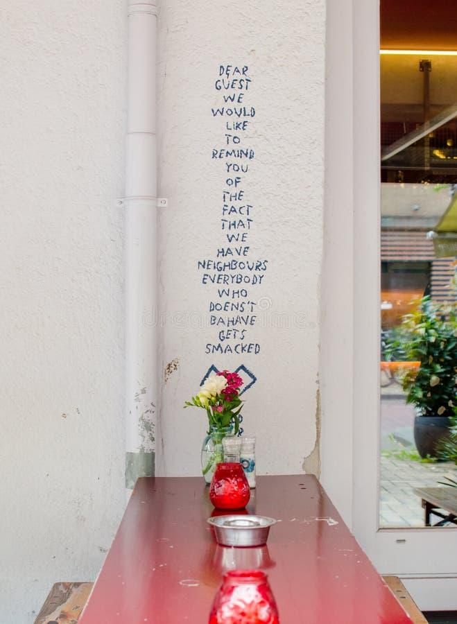 """Адвокатура """"Basquiat """"в улице Javastraat, Oost, Амстердаме, Нидерланд Взгляд стены с таблицей текста и улицы красной с подсвечник стоковое изображение rf"""