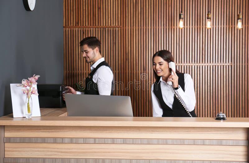 Администраторы работая на столе в лобби стоковая фотография rf