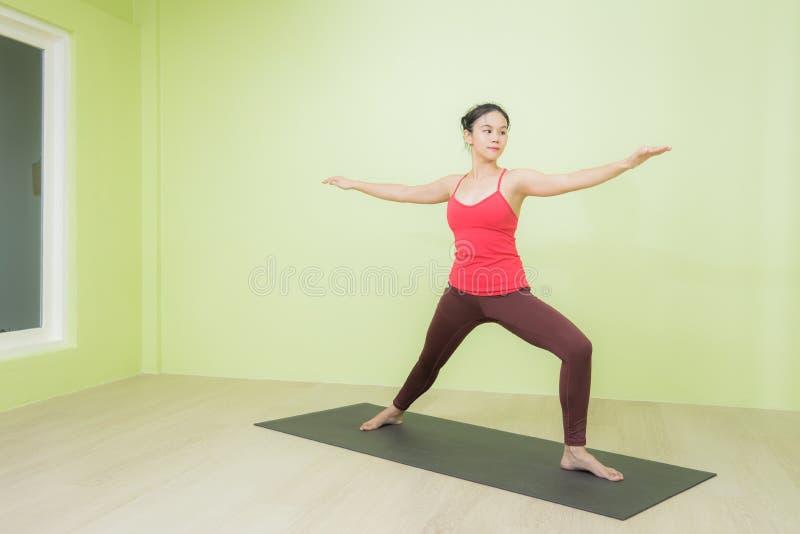 Азиатка, которая делает воин, позирует йогу стоковое фото rf