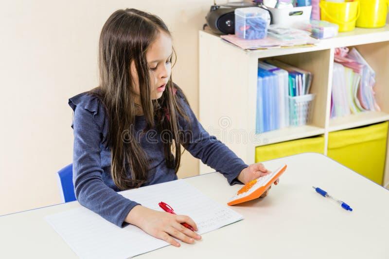 Азиатская американская девушка используя калькулятор стоковые изображения
