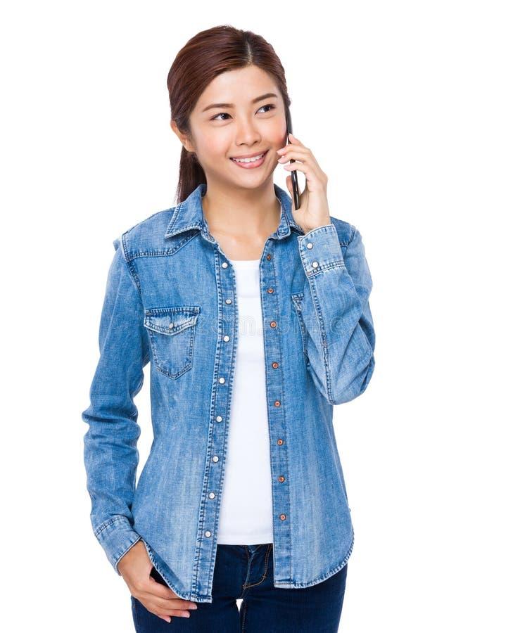 Азиатская беседа женщины к мобильному телефону стоковые фотографии rf