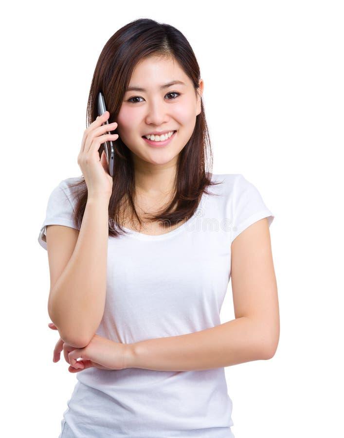 Азиатская беседа женщины к мобильному телефону стоковые изображения rf