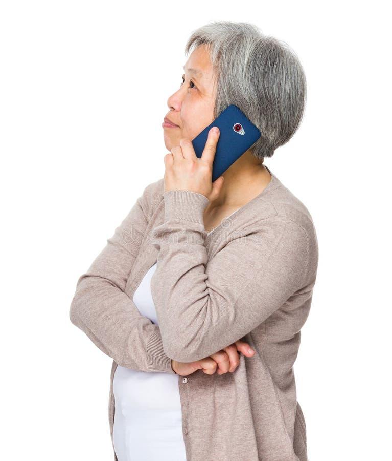Азиатская беседа женщины к мобильному телефону стоковая фотография rf