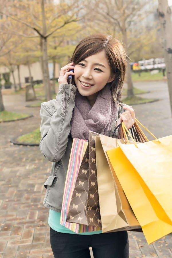 Азиатская беседа женщины на хозяйственных сумках владением телефона стоковая фотография rf