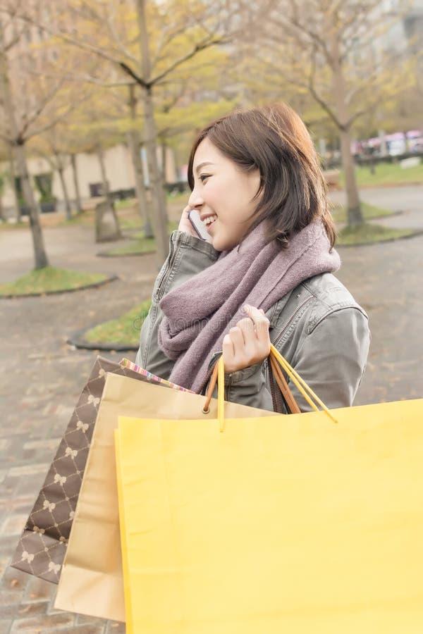 Азиатская беседа женщины на хозяйственных сумках владением телефона стоковые изображения