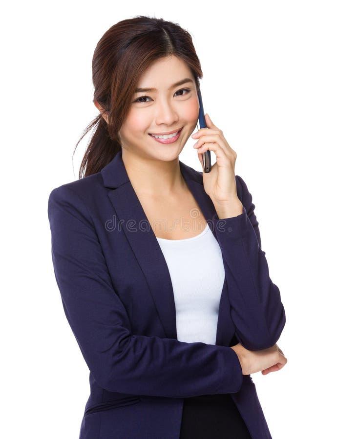 Азиатская беседа коммерсантки к мобильному телефону стоковое изображение rf