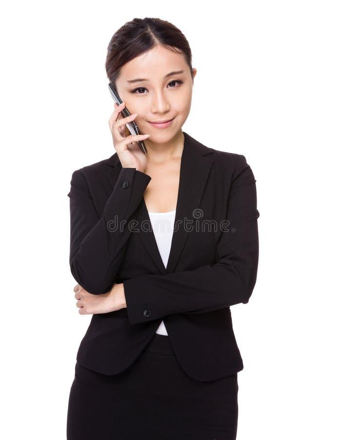 Азиатская беседа коммерсантки к телефону стоковая фотография