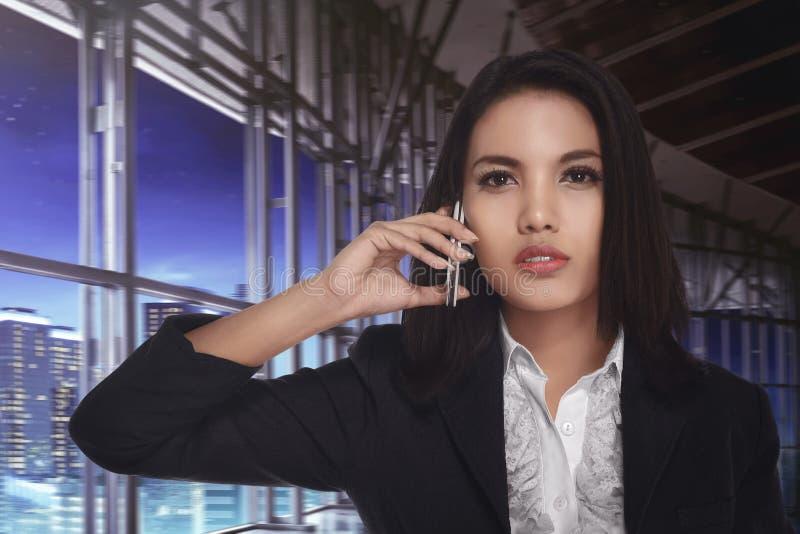 Азиатская бизнес-леди вызывая на телефоне последней на ноче стоковая фотография