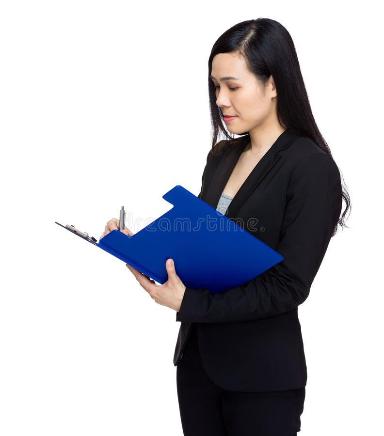 Азиатская бизнес-леди пишет на доске сзажимом для бумаги стоковые изображения