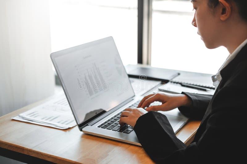 Азиатская бизнес-леди используя ноутбук работая новый проект обсуждая данные по диаграммы нового плана финансовые стоковое изображение rf