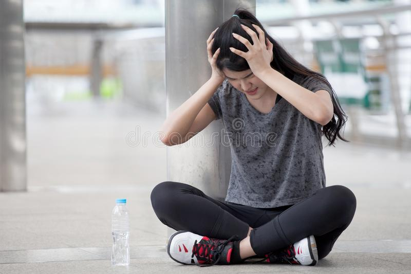 азиатская боль мигрени головной боли молодой женщины фитнеса во время разминки работая с бутылкой с водой на улице в городском го стоковое изображение rf