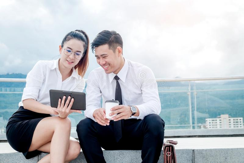 Азиатская встреча пар дела используя стойку цифровой таблетки внешнюю стоковое фото