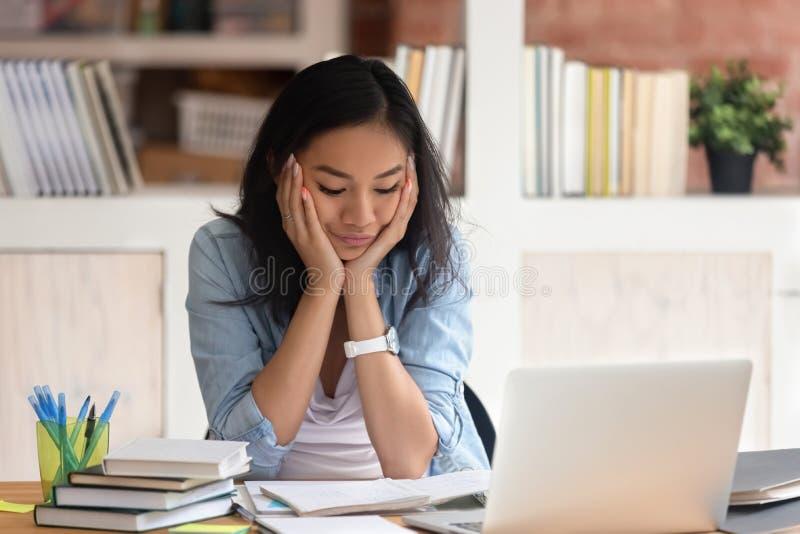 Азиатская вымотанная девушка студента имея серию задач чувствует несчастной стоковая фотография rf