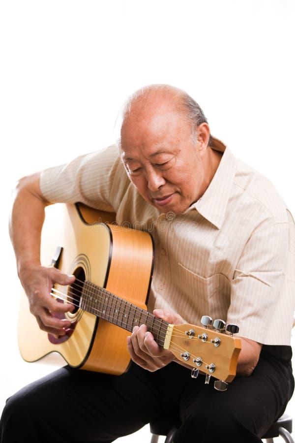 азиатская гитара играя старший стоковые фотографии rf