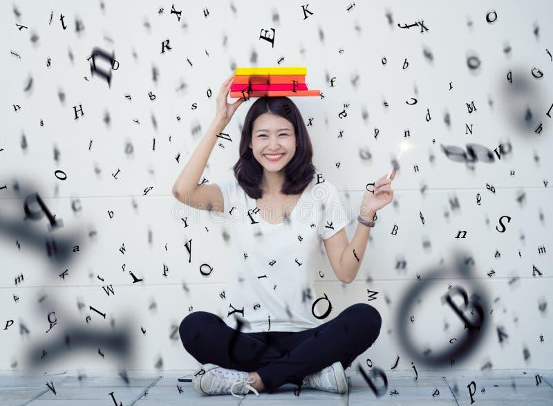 Азиатская дама сидя с книгой и дождем алфавита стоковое фото rf