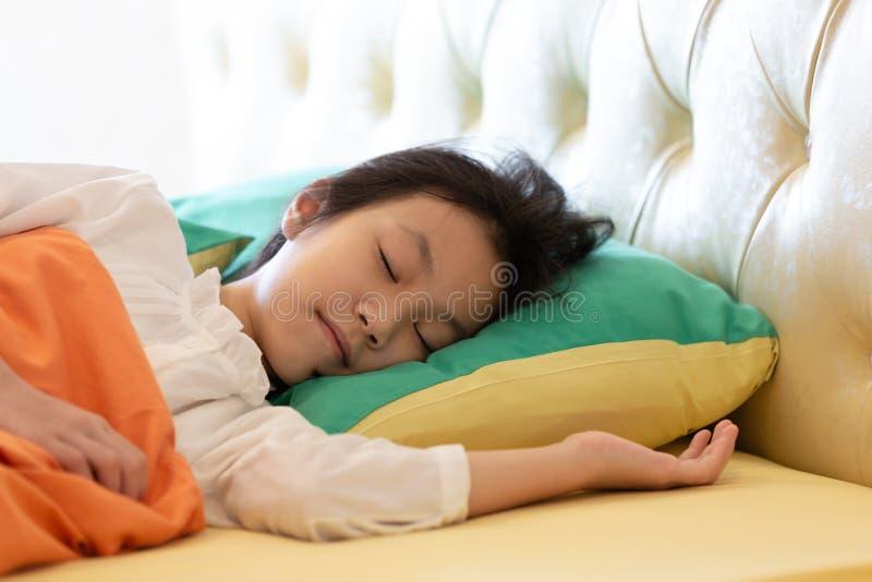 Азиатская девушка глубоко спать на ее кровати с меньшей усмехаясь мечтой, идет стоковое изображение rf