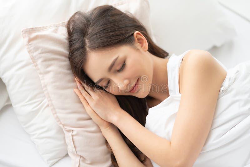 Азиатская девушка лежа в ее кровати в утре стоковая фотография rf