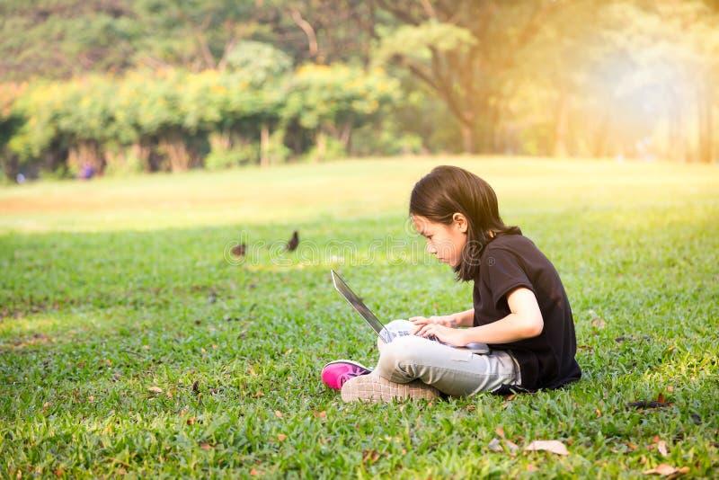 Азиатская девушка маленького ребенка использует ноутбук в на открытом воздухе парке, интернете и концепции образования стоковое фото