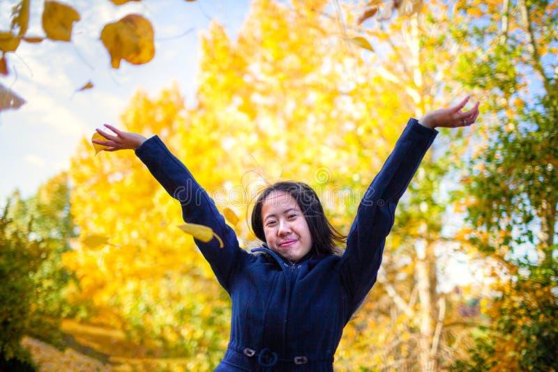 Азиатская девушка меча желтые листья осени в воздухе в парке стоковая фотография