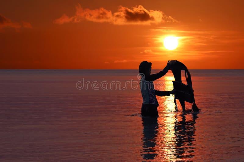 Азиатская девушка наслаждаясь со спасательным жилетом на пляже на заходе солнца, красной предпосылке неба на острове архипелага стоковое фото rf