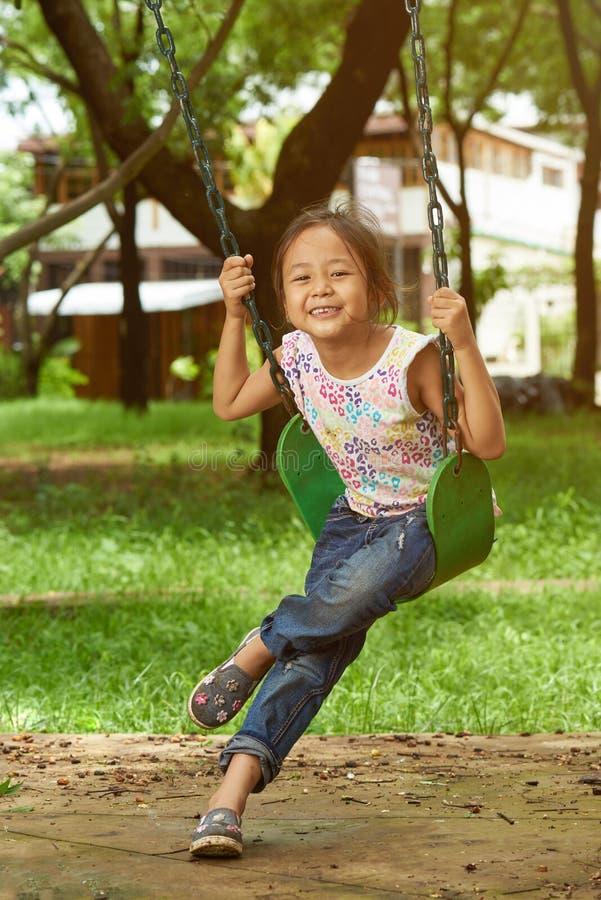 Азиатская девушка на качании играя на парке стоковые изображения rf