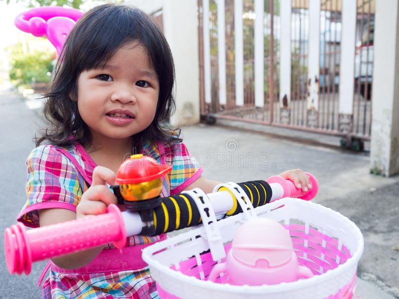 Азиатская девушка на розовом платье с новым розовым велосипедом Она усмехающся и счастлива получить новый велосипед стоковое фото rf