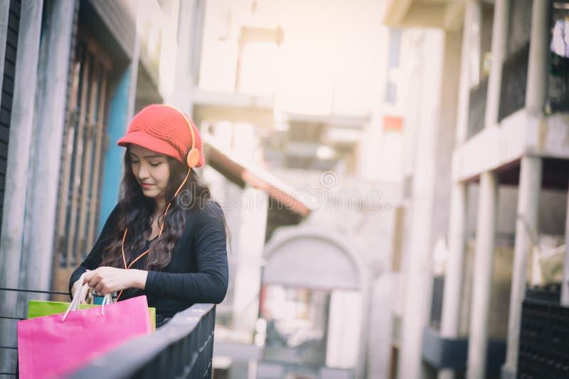 Азиатская девушка портрета имеет счастливую и слушая музыку с ходя по магазинам красочными сумками стоковое изображение rf