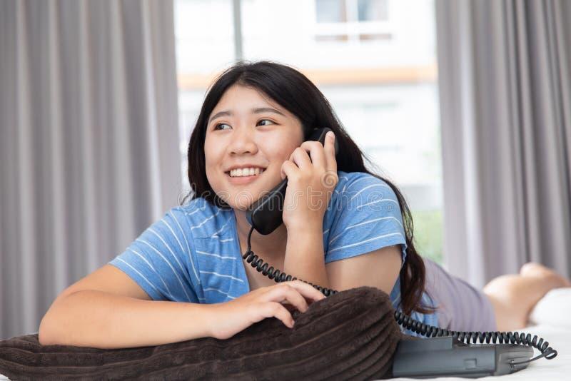Азиатская девушка предназначенная для подростков используя вызывать телефонный звонок назеиной линии стоковые изображения rf