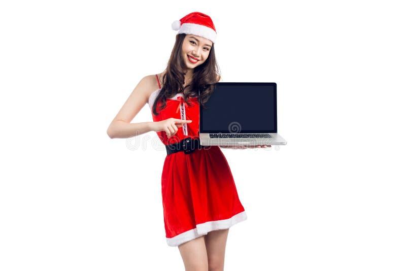 Азиатская девушка рождества с Санта Клаусом одевает держать iso компьтер-книжки стоковые изображения rf