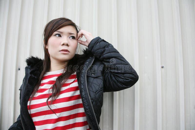 азиатская девушка смотря бортова к стоковое изображение