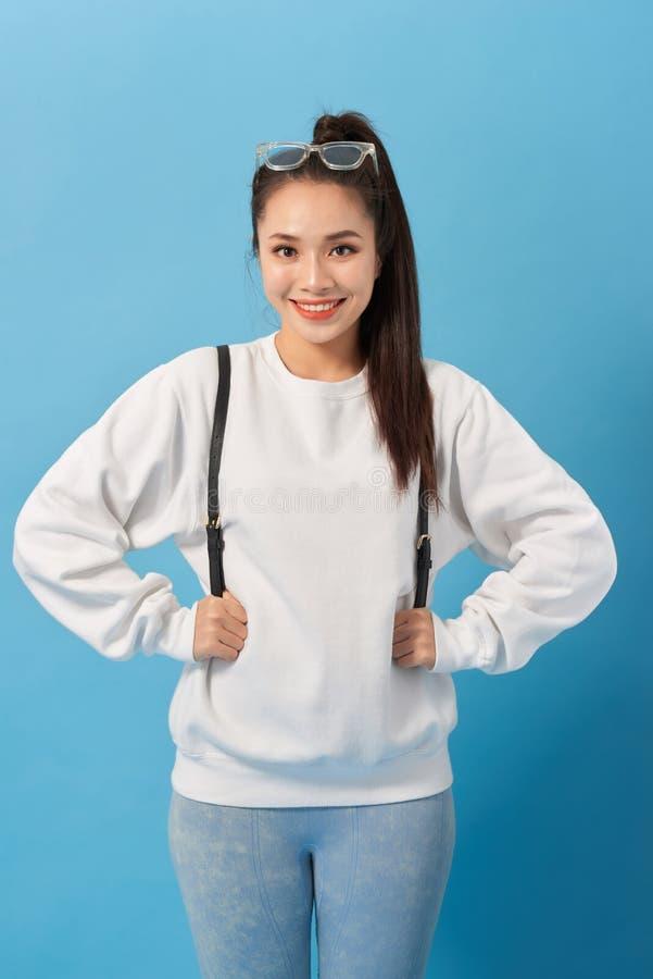 Азиатская девушка студента над изолированной голубой стеной счастливой и усмехаться стоковое фото rf