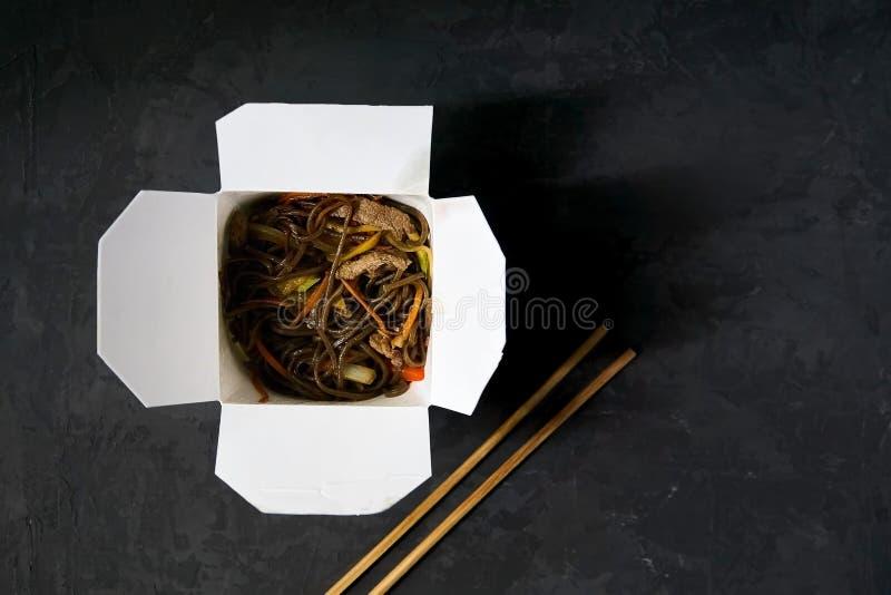 Азиатская доставка еды ресторана Лапши Soba с мясом, овощами и соевым соусом в белой коробке бумаги взятия-вне на черной предпосы стоковые фотографии rf