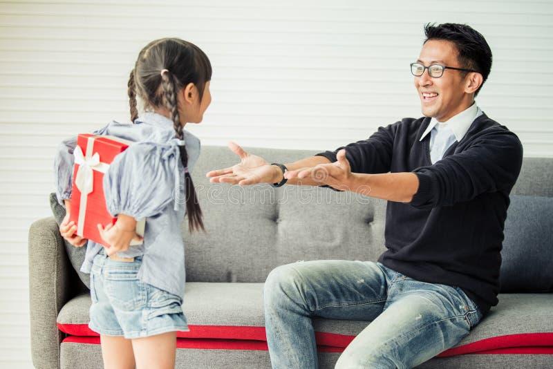 Азиатская дочь дает присутствующее для отца подарочная коробка сюрприза концепции стоковые изображения