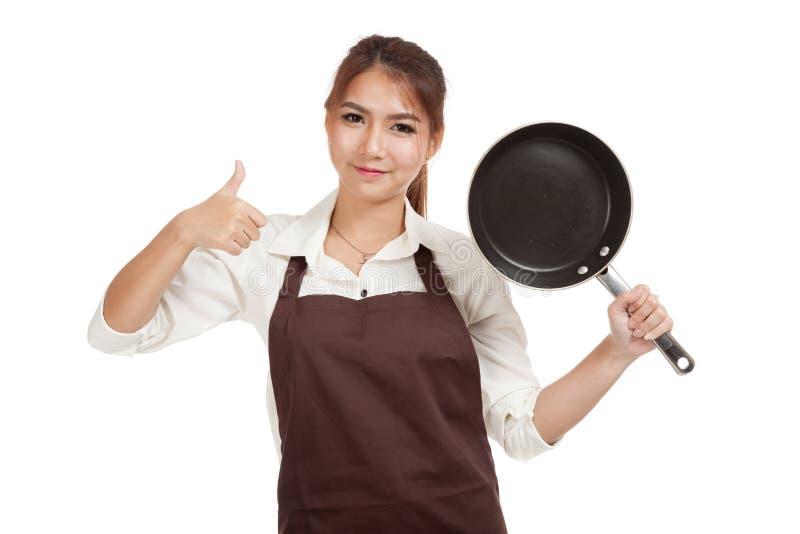Азиатская девушка варя большие пальцы руки вверх с сковородой стоковые фото
