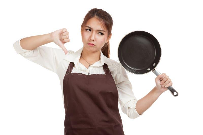 Азиатская девушка варя большие пальцы руки вниз с сковородой стоковая фотография rf