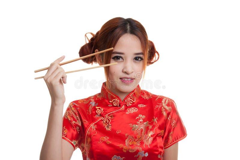 Азиатская девушка в китайском платье cheongsam с палочками стоковое фото